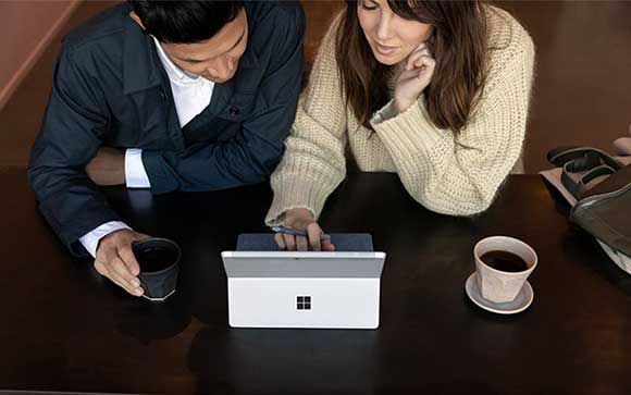 A woman using Microsoft Surface Go 2 with a man beside him looking on the device