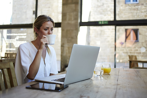 Working remotely woman while sipping coffee