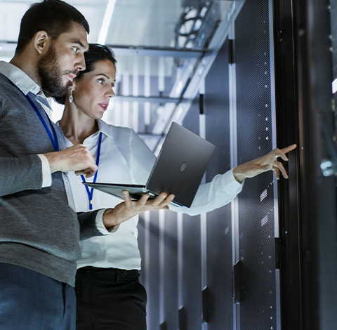 Two IT workers using a laptop in a data centre